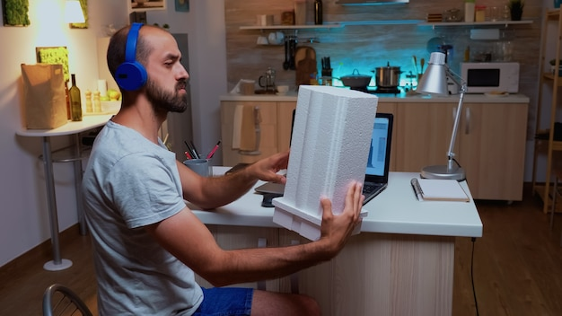 Architect holding building model while working on a project during night in home. industrial male employee studying prototype idea on personal computer showing cad software on device display