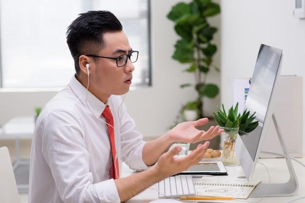 Архитектор в офисе разговаривает с клиентом по телефону с наушниками