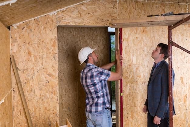 안전모를 쓴 건설 노동자를 바라보는 정장 재킷을 입은 건축가 미완성된 새 집 내부 수준으로 도어 프레임 측정