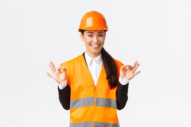 アーキテクトは完璧な計画を立てました。大丈夫なジェスチャーを示す安全ヘルメットの自信を持ってアジアの女性エンジニアは、すべてを制御し、優れた結果に満足し、白い背景に立っています
