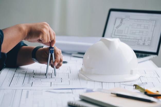 青写真に建築プロジェクトをスケッチする建築家の男建築とエンジニアリングの概念
