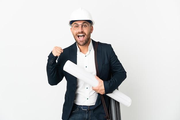 헬멧을 쓰고 우승자 위치에서 승리를 축하하는 흰색 배경에 고립 된 청사진을 들고 건축가 남자