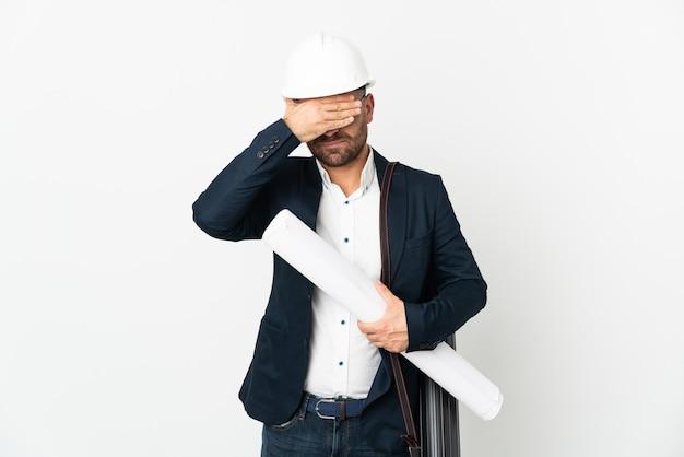 手で目を覆っている白い背景に分離されたヘルメットと青写真を保持している建築家の男。何かを見たくない
