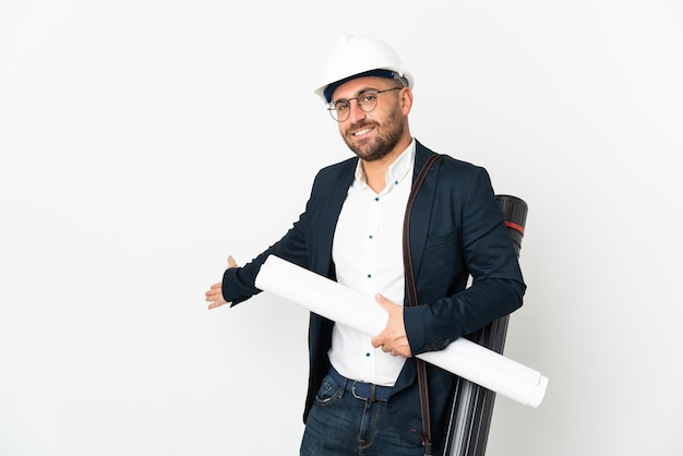 ヘルメットをかぶった建築家の男と白い背景に分離された青写真を持って、来て招待するために手を横に伸ばします