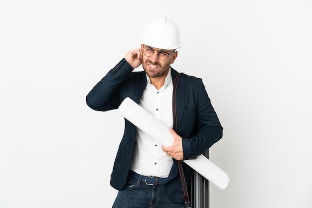ヘルメットと白い背景に分離された青写真を保持している建築家の男は欲求不満と耳を覆っています