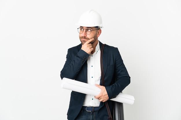Архитектор человек в шлеме и держит чертежи, изолированные на белом фоне, сомневаясь и думая
