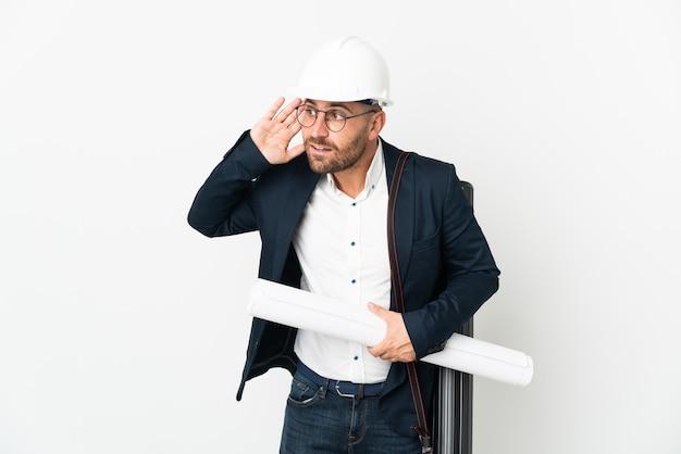 ヘルメットと白い背景で隔離の青写真を保持している建築家の男は、耳に手を置くことによって何かを聞いています