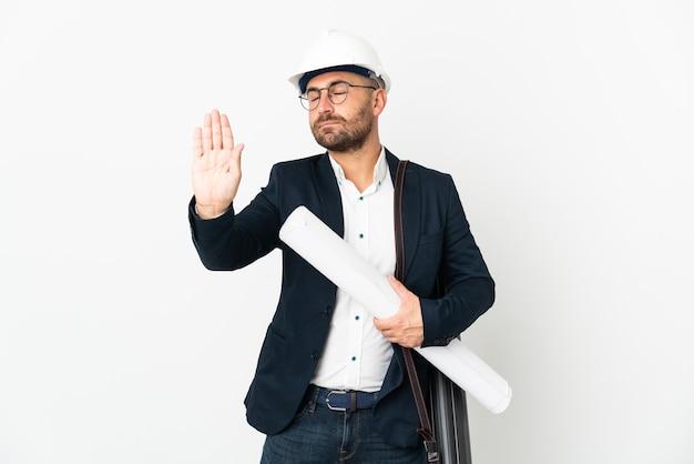 ヘルメットをかぶった建築家の男と白い背景に分離された青写真を保持して停止ジェスチャーを作成し、失望した