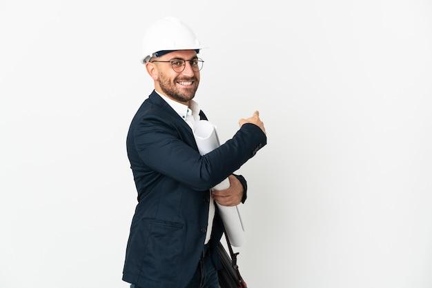 ヘルメットと後ろ向きの白い背景で隔離の青写真を保持している建築家の男