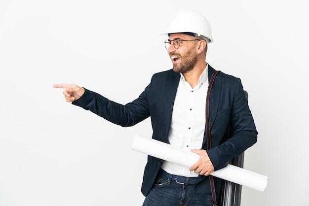 Архитектор человек в шлеме и держит чертежи, изолированные на белом фоне, указывая пальцем в сторону и представляет продукт