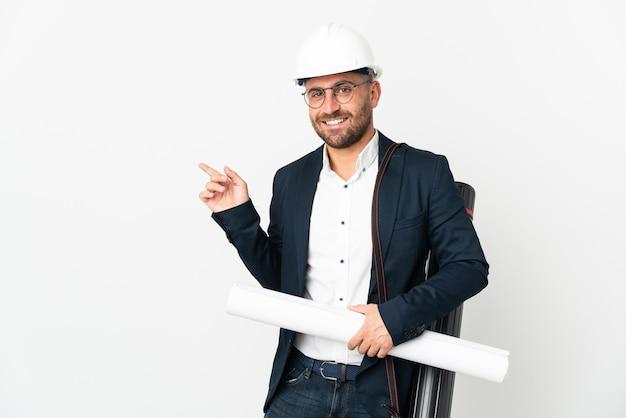 헬멧 건축가 남자와 측면에 손가락을 가리키는 흰색 배경에 고립 된 청사진을 들고