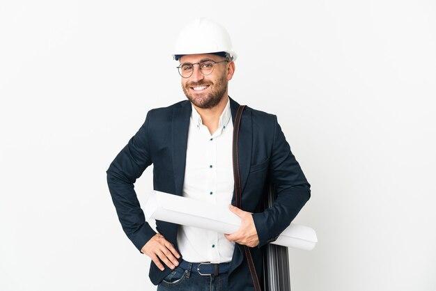 Архитектор человек в шлеме и держит чертежи, изолированные на белом фоне, позирует с руками на бедре и улыбается