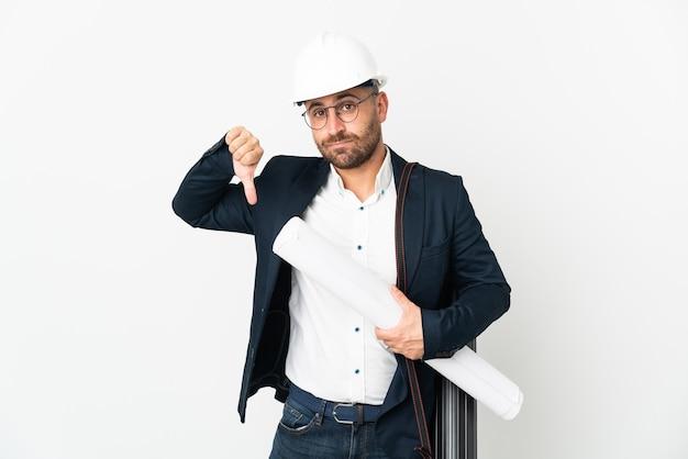 헬멧을 가진 건축가 남자와 부정적인 표현으로 엄지 손가락을 보여주는 흰색 배경에 고립 된 청사진을 들고