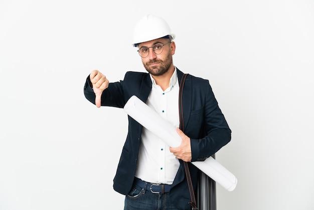 헬멧을 쓰고 흰색 배경에 격리된 청사진을 들고 부정적인 표정으로 엄지손가락을 아래로 내리는 건축가 남자