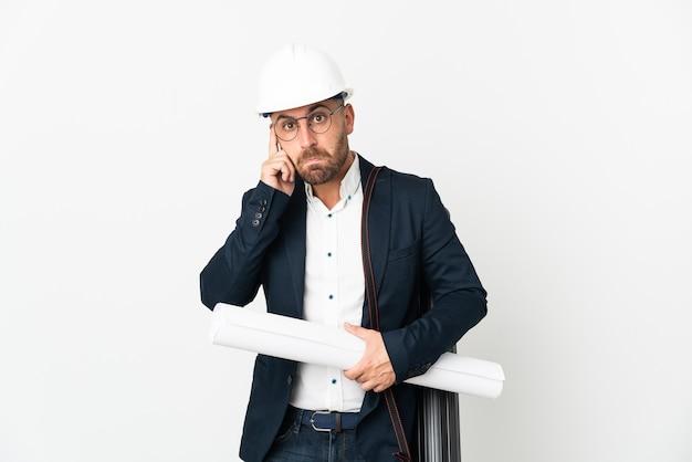 헬멧과 아이디어를 생각하는 흰색 배경에 고립 된 청사진을 들고 건축가 남자