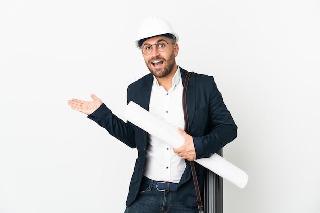 Архитектор мужчина в шлеме и держит чертежи, изолированные на белом фоне с шокированным выражением лица