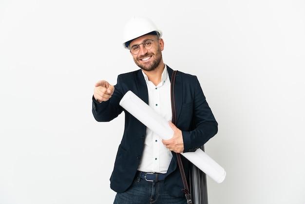 헬멧을 가진 건축가 남자와 행복 한 표정으로 앞을 가리키는 흰색에 고립 된 청사진을 들고