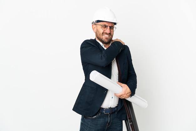 Человек-архитектор в шлеме и держит чертежи, изолированные на белом, страдает от боли в плече за то, что приложил усилие