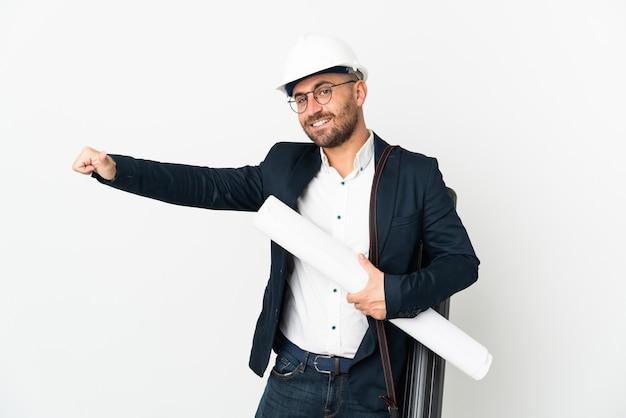 Человек-архитектор в шлеме и держит чертежи, изолированные на белой стене, показывая жест рукой вверх