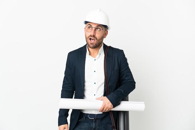 Человек-архитектор в шлеме и держит чертежи, изолированные на белой стене, глядя вверх и с удивленным выражением лица