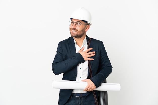 Архитектор человек в шлеме и держит чертежи, изолированные на белой стене, глядя вверх, улыбаясь