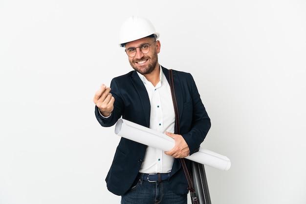Человек-архитектор в шлеме и держит чертежи, изолированные на белой стене, делая денежный жест