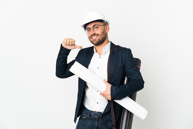 Человек-архитектор в шлеме и держит чертежи, изолированные на белой стене, гордый и самодовольный