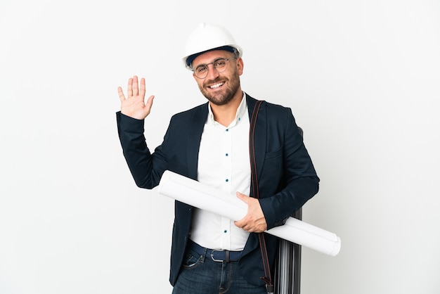 幸せな表情で手で敬礼する白い壁に分離されたヘルメットと青写真を保持している建築家の男