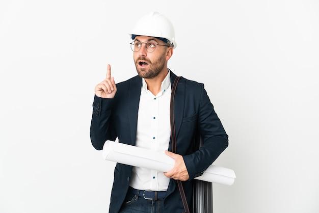 Человек-архитектор в шлеме и держит чертежи, изолированные на белой стене, думая об идее, указывая пальцем вверх