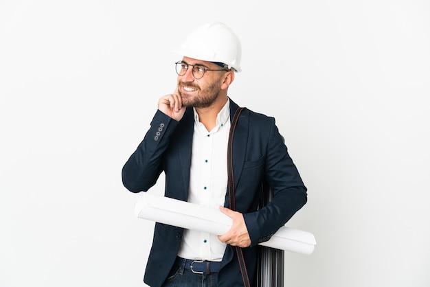 헬멧을 가진 건축가 남자와 찾는 동안 흰 벽 생각에 고립 된 청사진을 들고
