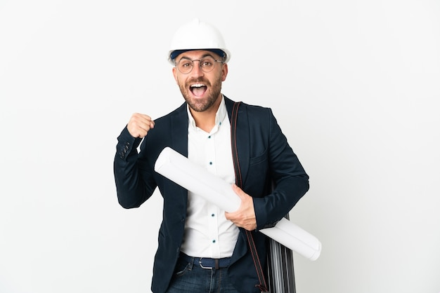 Architect man with helmet and holding blueprints isolated on white background celebrating a victory in winner position