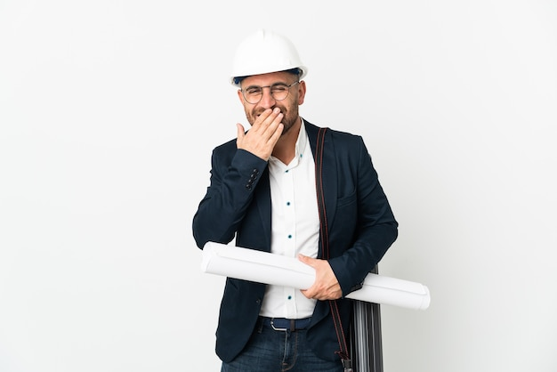 Architect man with helmet and holding blueprints isolated on white background happy and smiling covering mouth with hand