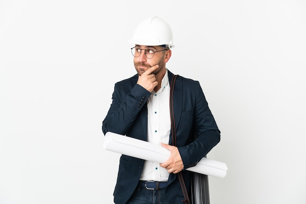 Architect man with helmet and holding blueprints isolated on white background having doubts and thinking