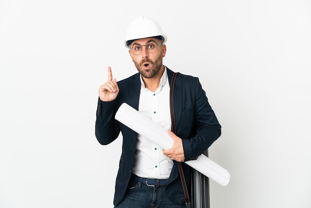 Architect man with helmet and holding blueprints isolated on white background intending to realizes the solution while lifting a finger up