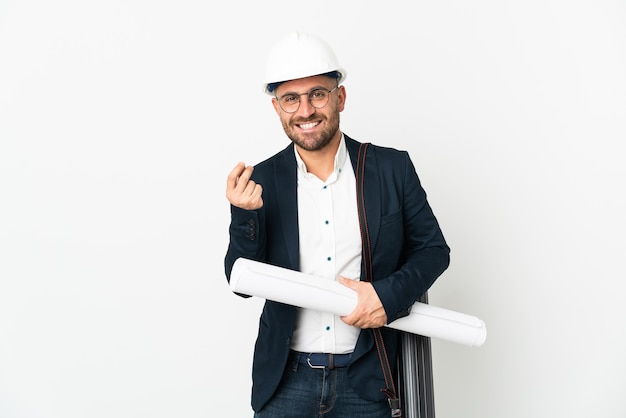 Architect man with helmet and holding blueprints isolated on white background making money gesture