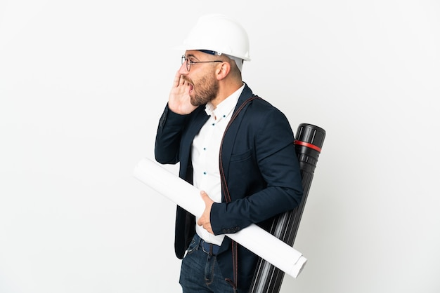 Architect man with helmet and holding blueprints isolated on white background shouting with mouth wide open to the side