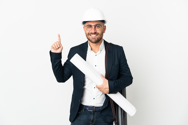 Architect man with helmet and holding blueprints isolated on white background showing and lifting a finger in sign of the best