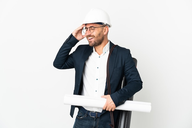 Architect man with helmet and holding blueprints isolated on white background smiling a lot