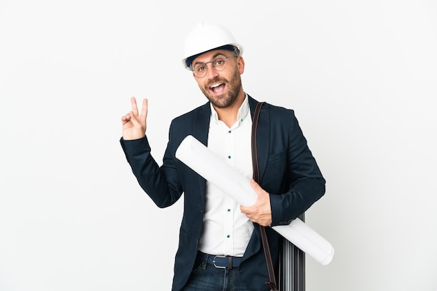 Architect man with helmet and holding blueprints isolated on white background smiling and showing victory sign