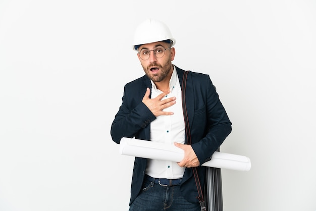 Architect man with helmet and holding blueprints isolated on white background surprised and shocked while looking right