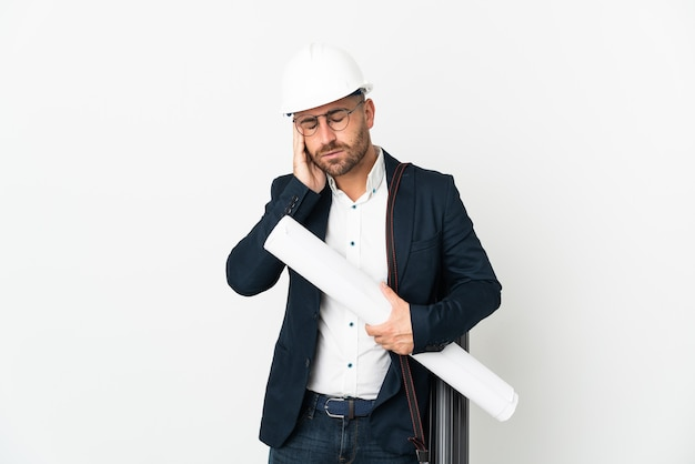 Architect man with helmet and holding blueprints isolated on white background with headache
