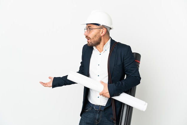 Architect man with helmet and holding blueprints isolated on white background with surprise expression while looking side