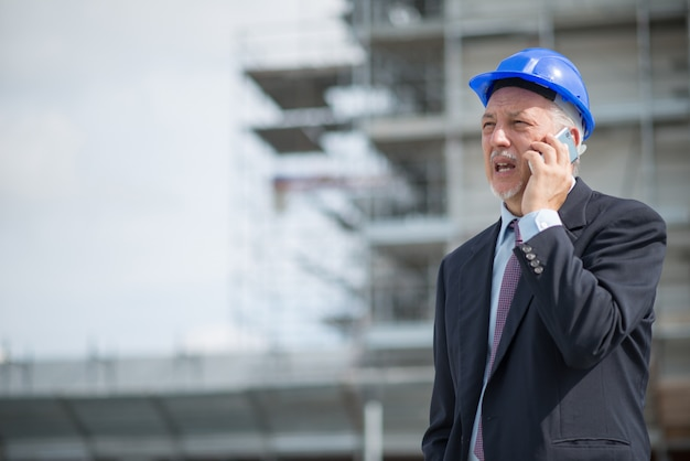 Architect manager talking on the cellphone in front of construction site