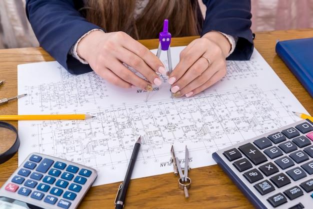 建築家は建築図面を測定して計算し、クローズアップ
