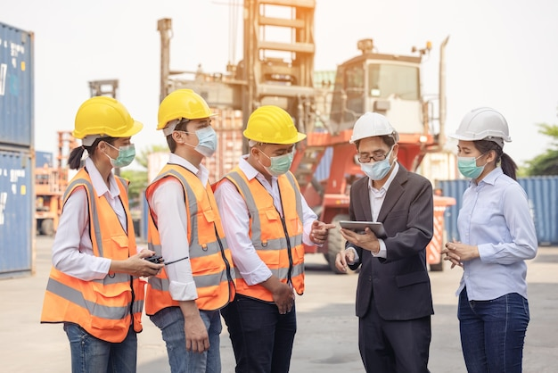 컨테이너 화물 항구에서 확인 작업을 하는 엔지니어 및 부두 작업자 직원의 건축가