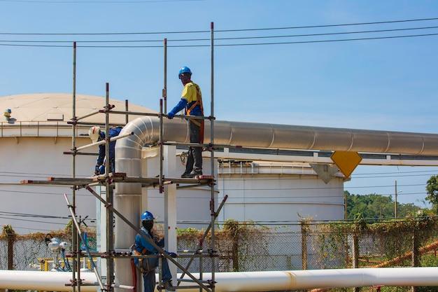비계 파이프라인에 현장 건설 노동자의 건축가. 진행 중인 작업을 위한 플랫폼을 제공하는 광범위한 비계. 비계로 둘러싸인 지붕 위를 걷는 남자