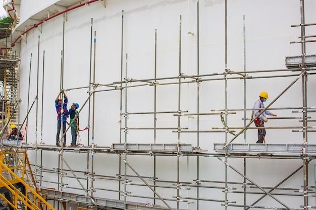 足場タンクオイルの現場建設作業員の建築家。進行中の作業のためのプラットフォームを提供する広範な足場。足場に囲まれた屋根の上を歩く男性