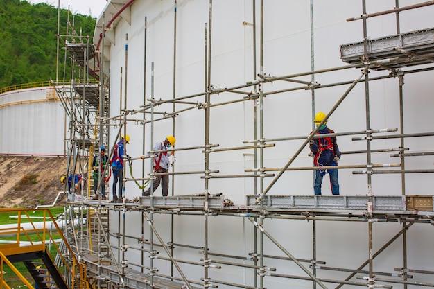 비계 탱크 오일에 현장 건설 노동자의 건축가. 진행 중인 작업을 위한 플랫폼을 제공하는 광범위한 비계. 비계로 둘러싸인 지붕 위를 걷는 남자