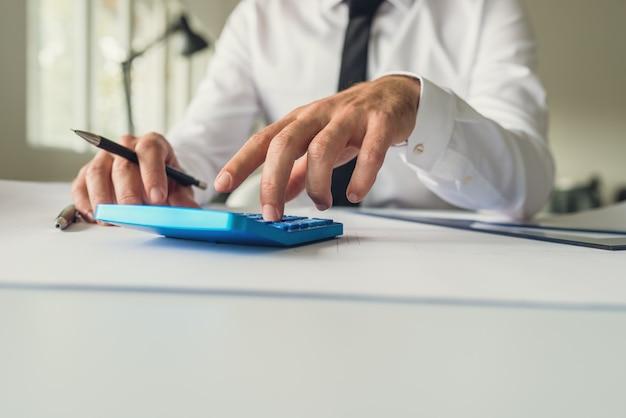 건축가 또는 디자이너는 자신의 테이블에 연필과 통치자를 들고 자신의 프로젝트에서 작업하면서 계산기를 사용하여 그의 사무실 책상에 앉아 있습니다.