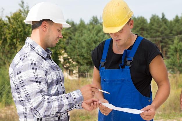 建築家またはエンジニアが、現場で一緒に立っているときにハンドヘルドドキュメントを指している建設作業員またはビルダーに何かを説明します